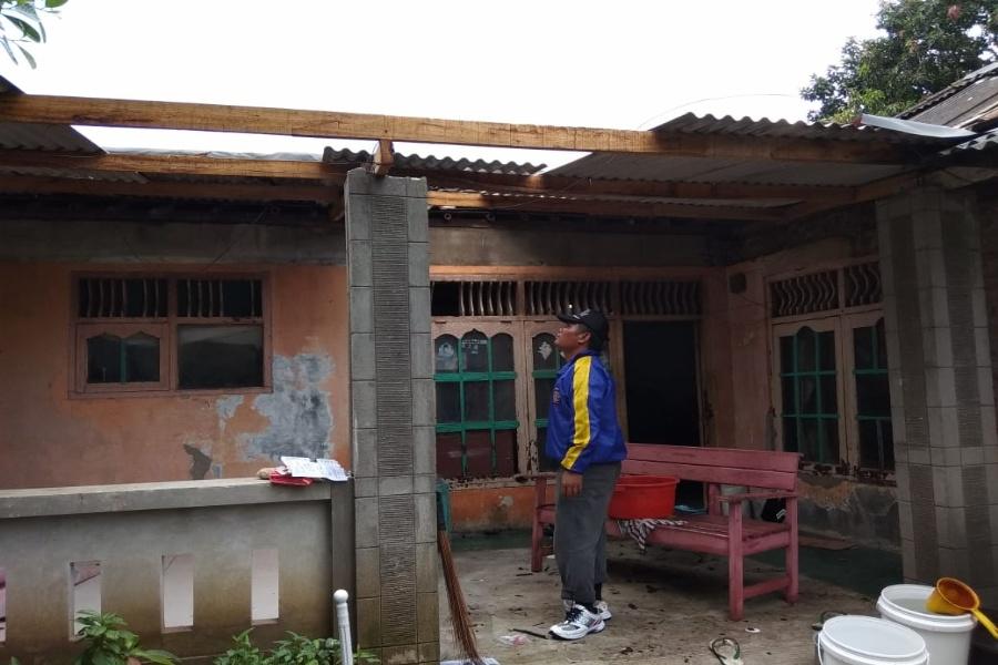 Salah seorang relawan Tagana saat mengecek rumah yang terkena puting beliung. (BantenHits.com/ Engkos Kosasih)